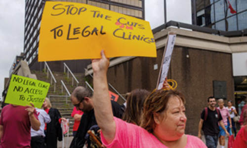 protest holding a Stop Legal Cuts sign